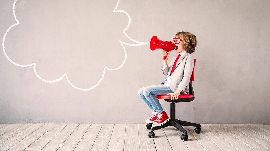 Ein Kind sitzt auf einem Schreibtischstuhl und ruft durch ein rotes Megafon. Eine gezeichnete Sprechblase kommt aus dem Megafon.