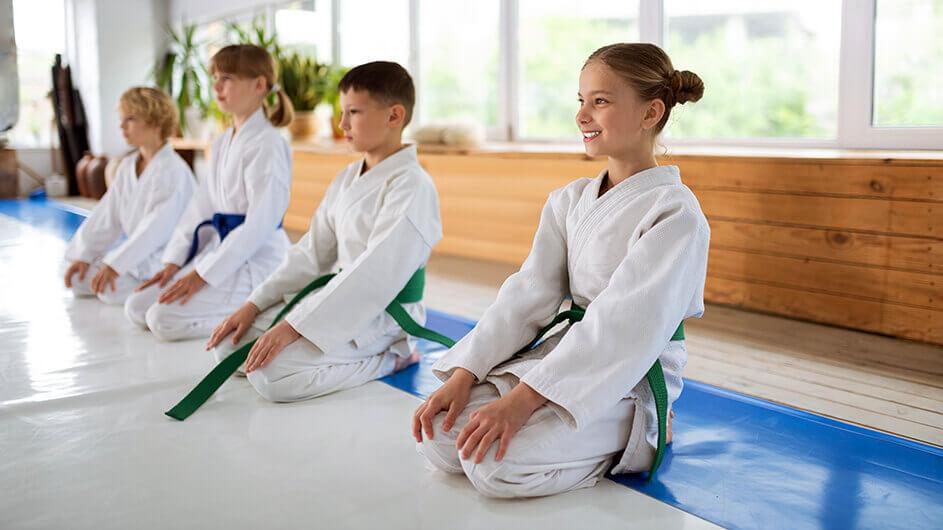 Vier Kinder beim Training einer asiatischen Kampfsportkunst zur Selbstverteidigung. Sie sitzen nebeneinander. Das vorderste Mädchen hat zwei Zöpfe und lächelt.