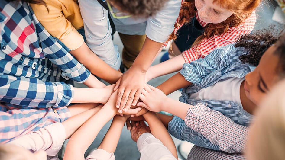 Eine Gruppe Kinder steht im Kreis. Sie legen in der Mitte des kreises ihre Hände aufeinander. Ein Zeichen für Freundschaft und Teamgeist.