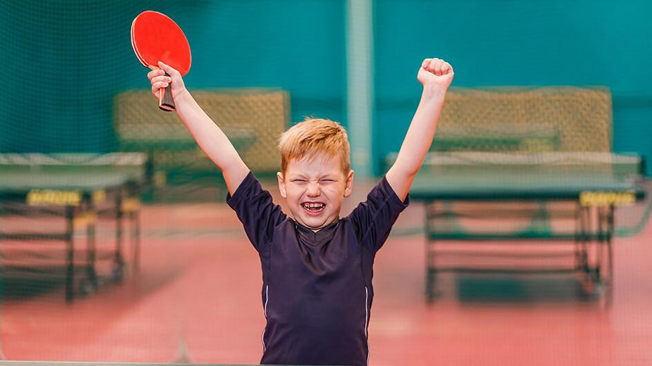 Jubelndes Kind beim Tischtennisspielen: Ein Junge freut sich in einer Sporthalle mit hochgerissenen Armen und einem breiten Lächeln.