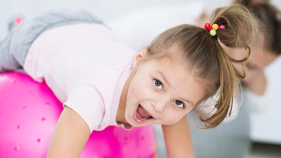 Ein Mädchen liegt lächelnd auf einem Gymnastikball und macht Zuhause Sport.