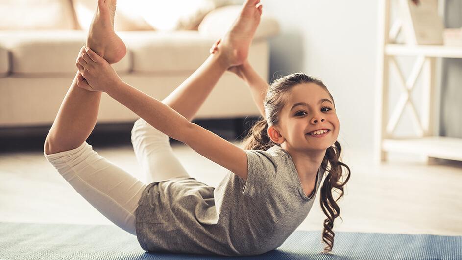 Ein Mädchen liegt mit dem Bauch auf einer Yogamatte und hält hinterrücks seine hochgehobenen Beinen mit den Händen fest. Das Kind lächelt.