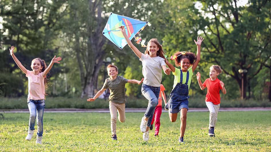 Eine gruppe fröhlicher Kinder beim Spielen mit einem Drachen: Die Mädchen und Jungen laufen über eine Wiese, lachen und die Sonne scheint. Auf dem Drachen ist ein Segelboot aufgedruckt.