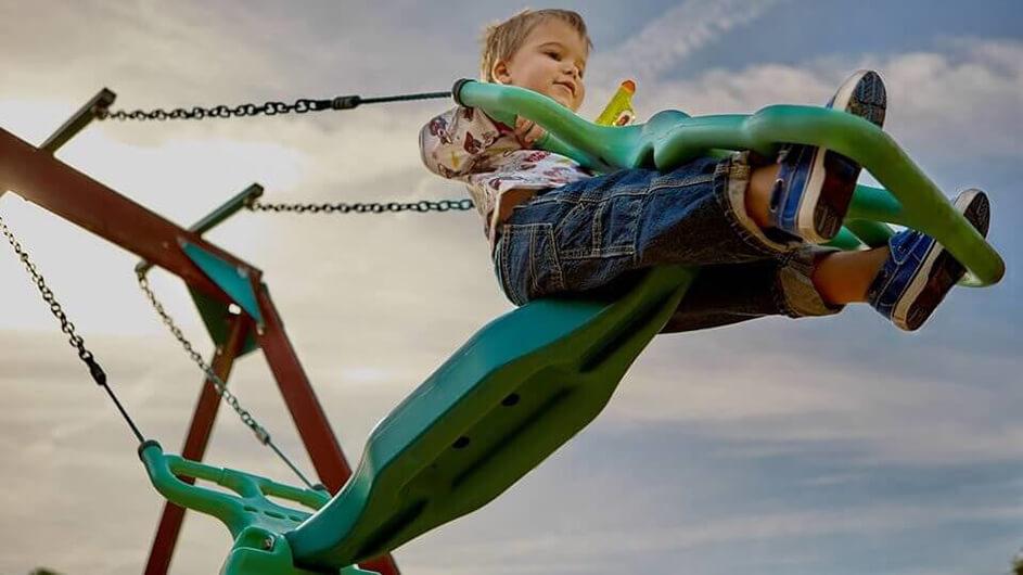 Ein Junge schaukelt auf einer Schaukel, die auf einem Kinderspielplatz steht.