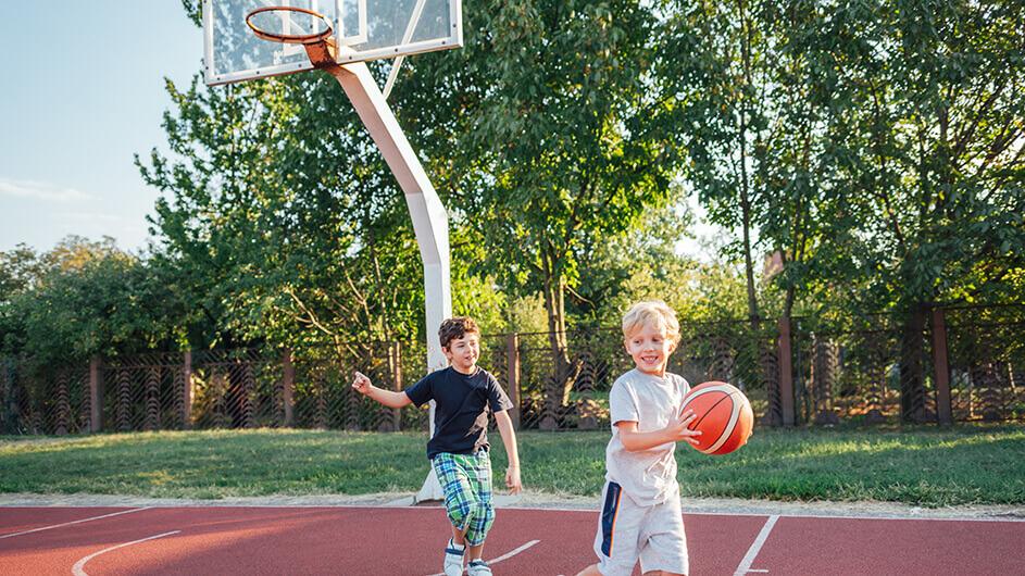 Zwei kleine Jungen draußen beim Basketballspielen bei schönem Wetter.