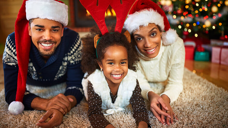Glückliche Familie an Weihnachten mit Weihnachtsmützen
