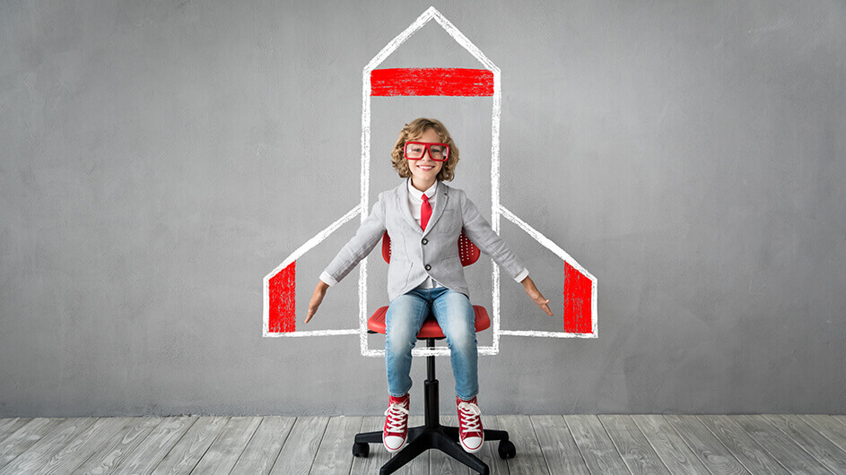 Ein Kind mit Blazer und Brille sitzt auf einem Bürostuhl und streckt die Arme aus - hinter ihm ist eine Rakete an die Wand gemalt