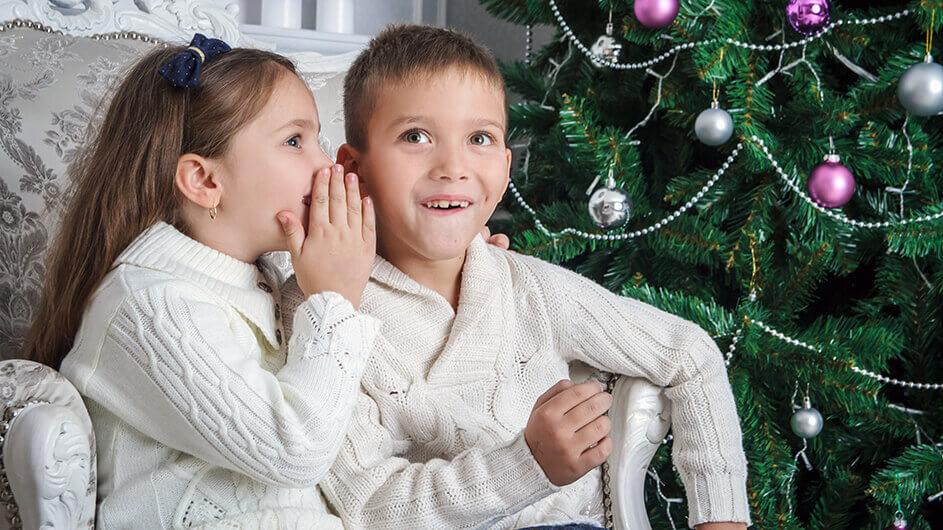 Die Schwester flüstert ihrem bruder etwas ins Ohr. Beide lächeln und sitzen vorm geschmückten Weihnachtsbaum.