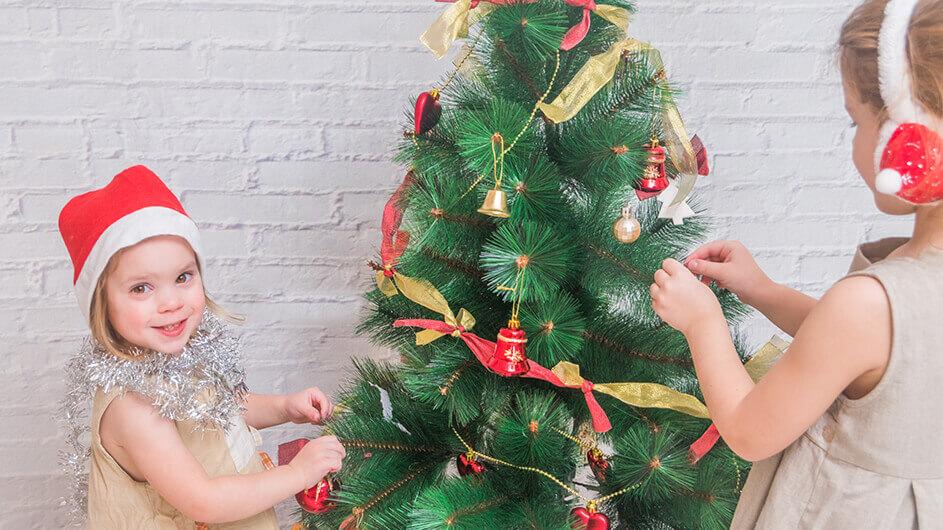 Zwei Mädchen schmücken lächelnd den Weihnachtsbaum
