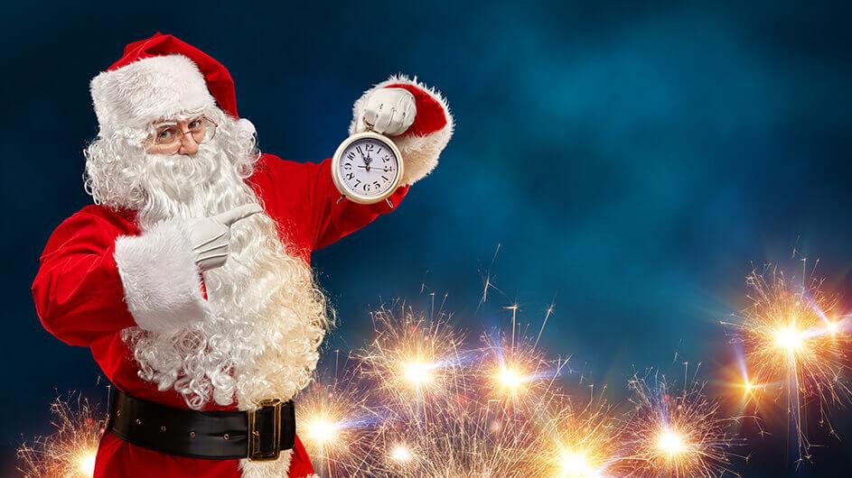 Der Weihnachtsmann zeigt auf einer Uhr, die auf 5 vor 12 uhr steht. Im Hintergrund ist ein Feuerwerk zu sehen.
