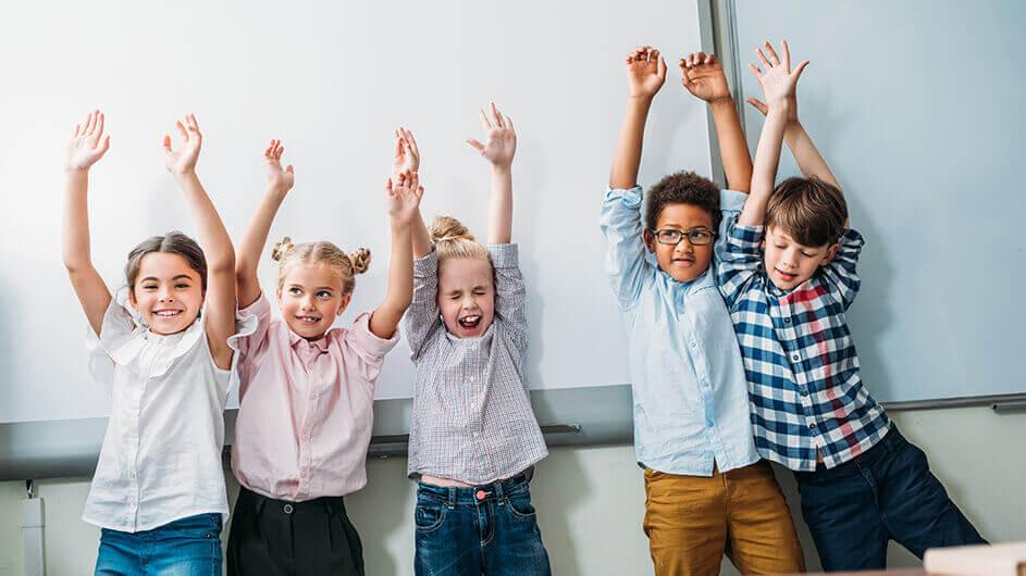 Fröhliche Kinder heben fröhlich die Arme vor einem Whiteboard in einer Kinder-Uni