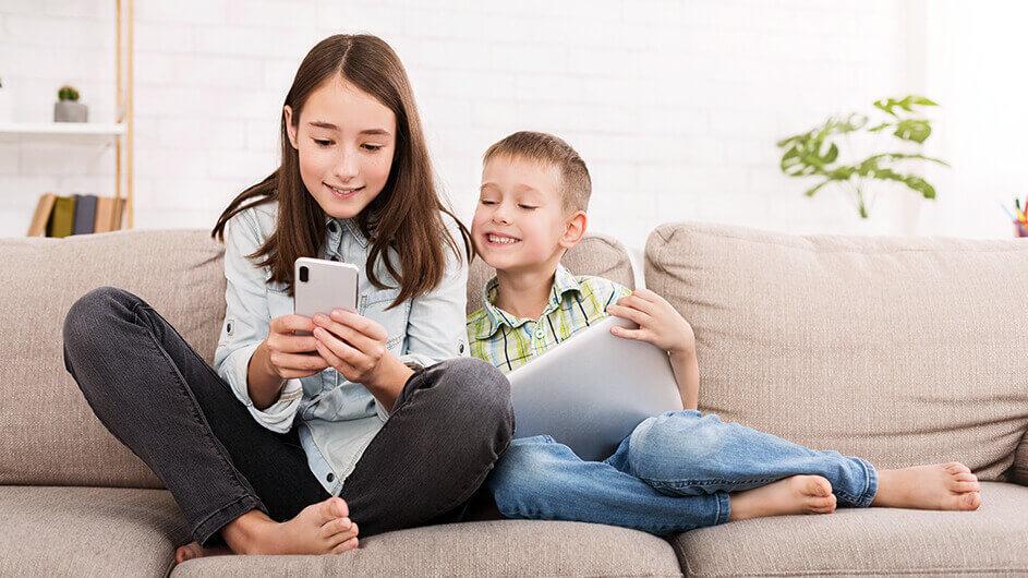 Zwei Geschwister sitzen zuhause auf dem Sofa und spielen mit Smartphone und Tablet Kinder-Apps. Beide lächeln.