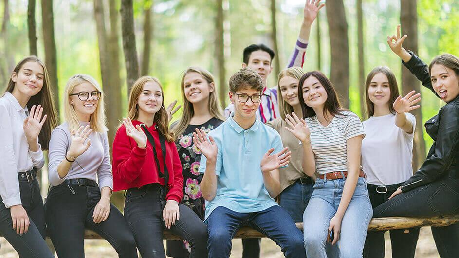Jugendliche bzw. TeenagerInnen auf einer Jugendmesse: Sie winken der/dem Fotografin fröhlich zu.