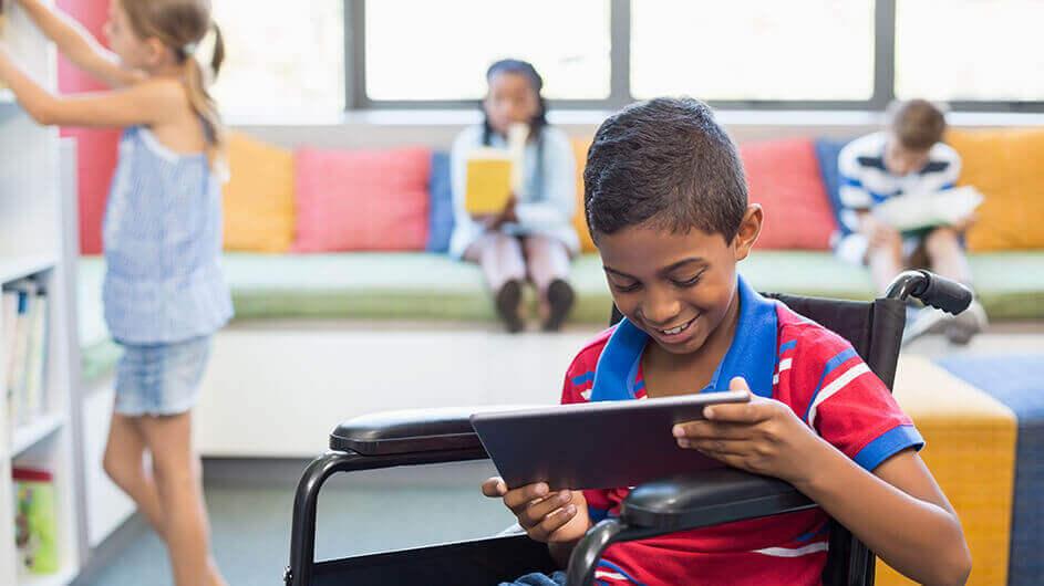 Ein Junge im Rollstuhl nutzt in einer Bibliothek ein Tablet. Er lächelt. Hinter ihm stehen und sitzen andere Kinder mit Büchern.