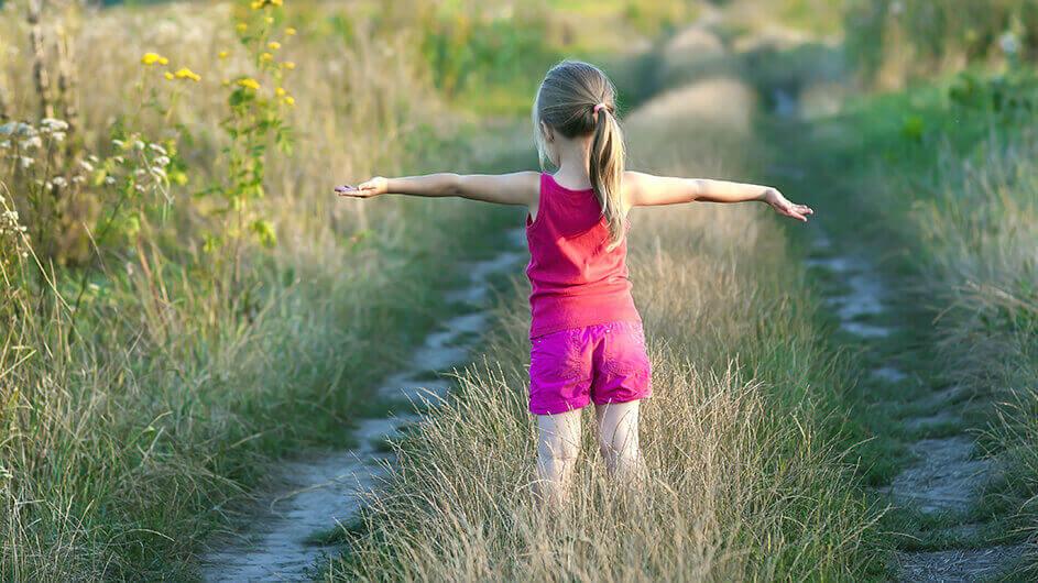 Kind barfuß auf einem Weg: Das Mädchen streckt freudig die Arme nach links und rechts