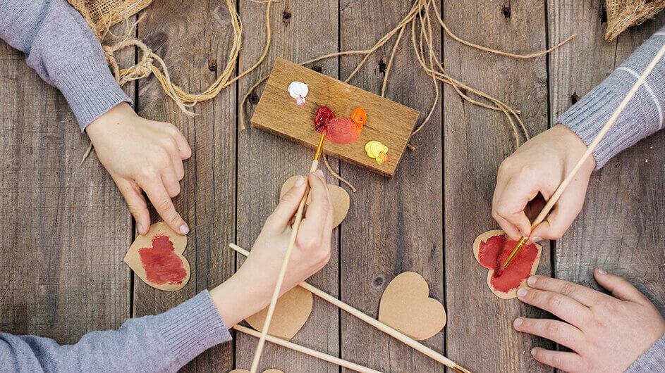 Kinder basteln und bemalen Papierherzen am Valentinstag