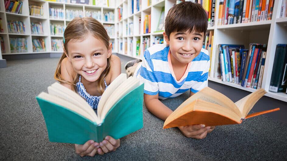Lachende Kinder liegen lesend mit Büchern auf dem Boden einer Bibliothek