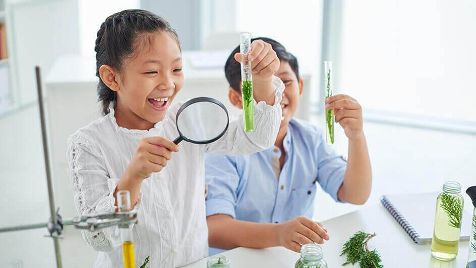 Kinder beim Experimentieren in einer Kinder-universität mit Reagenzgläsern und einer Lupe. Sie freuen sich.