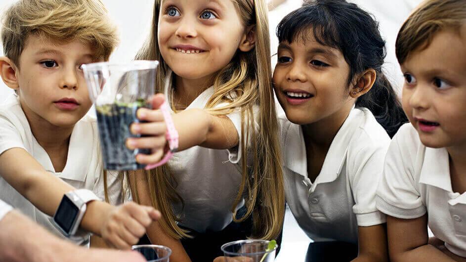 Fröhliche Kinder beim Experimentieren mit Pflanzen in der Kinder-Uni