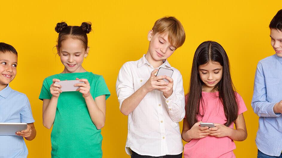 Lächelnde Kinder spielen oder lernen mit Kinder-Apps auf Smartphones und Tablets