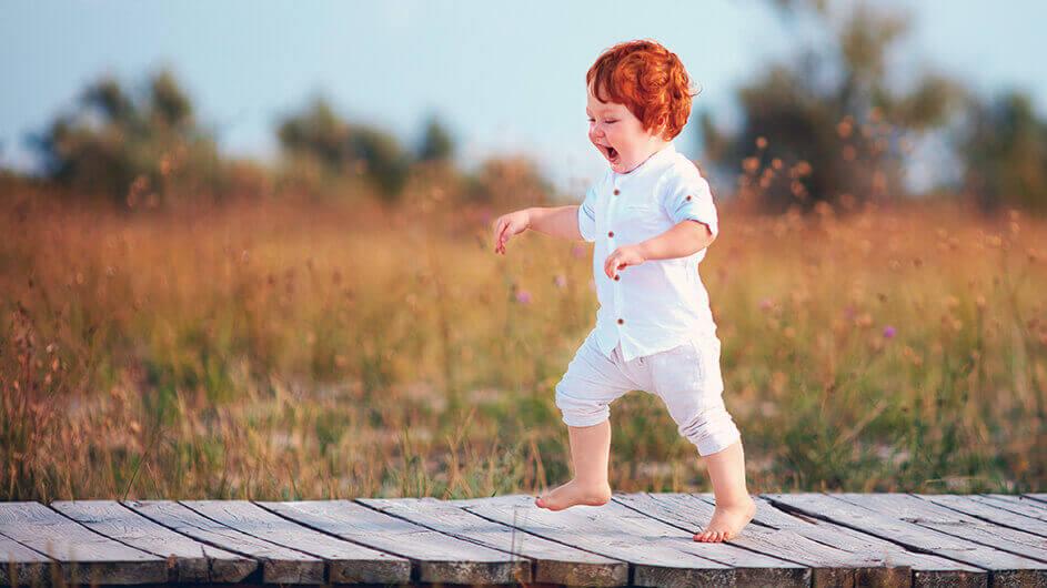 Ein kleiner Junge läuft barfuß jubelnd über einen Steg durch eine Sommerwiese