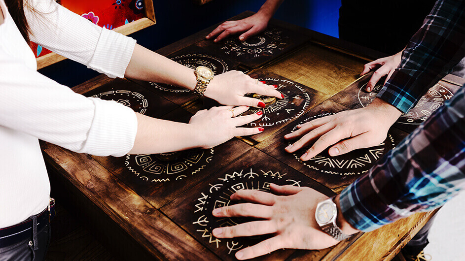 Jugendliche bzw. Erwachsene beim Lösen eines Escape Games in einem Escape Room: Sie haben die Hände auf Drehscheiben im mexikanischen Stil gelegt, die sie zum Lösen des Rätsels richtig drehen müssen