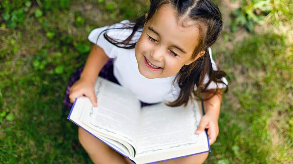 Ein Mädchen sitzt auf einer grünen Wiese und liest ein Buch: Gerade hat es lächelnd die Augen geschlossen, um sich die Welt des Buches vorzustellen.