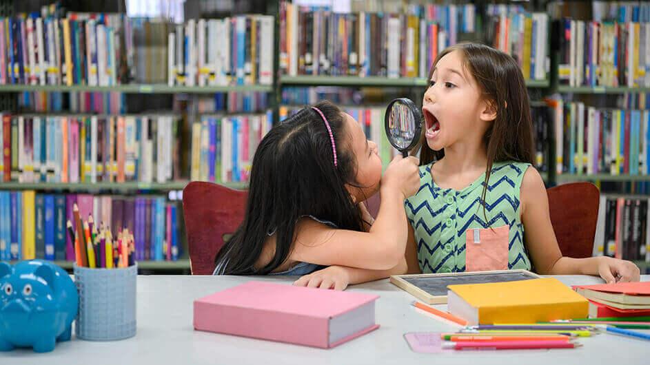 Zwei Mädchen lesen und spielen in einer Bibliothek mit einer Lupe