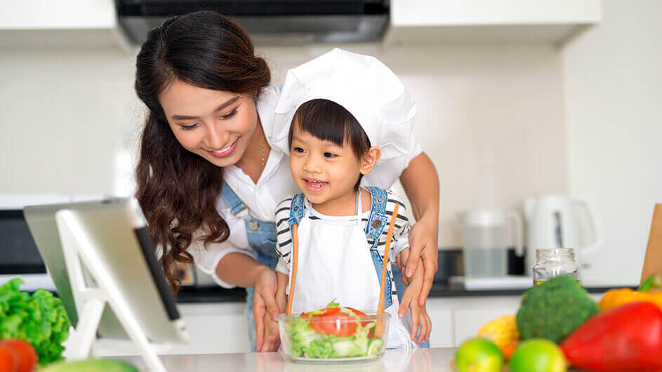 Mutter und Kind kochen gemeinsam in der Küche Salat