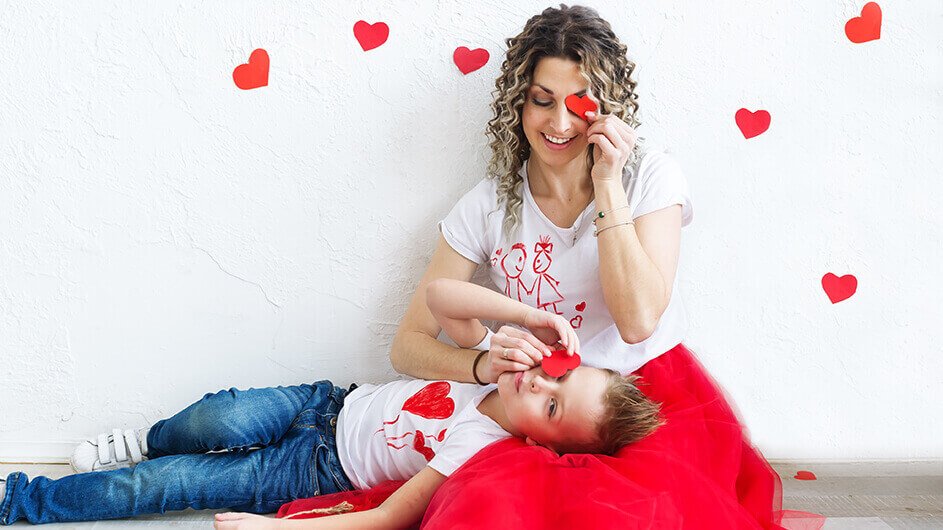 Mutter und Sohn Zuhause mit Herzen aus Papier und Herz-Dekoration an Valentinstag