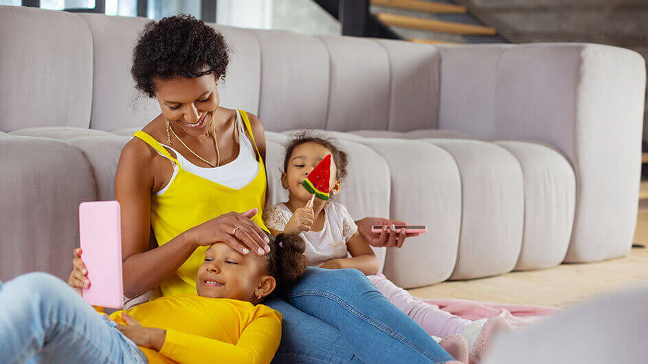 Mutter und zwei Töchter beim Spielen von Kinder-Apps: Alle lächeln und liegen entspannt auf dem Sofa.
