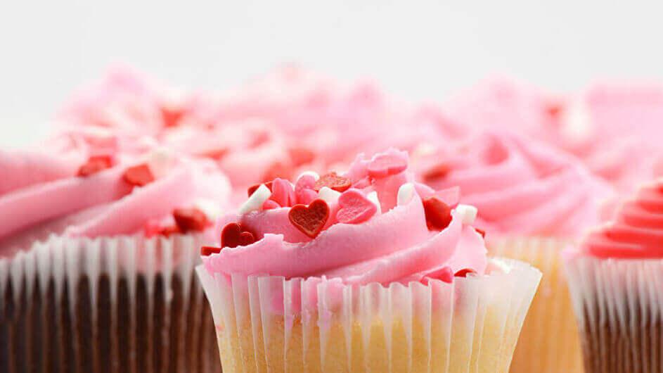 Rosa Cupcakes mit Sahnehaube und Herzchen zum Valentinstag: In ihnen versteckt sich eine kleine Liebes-Nachricht