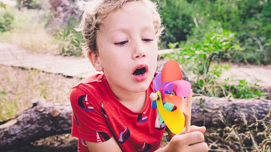 Ein Junge pustet ein Windrad bzw. eine Windmühle an