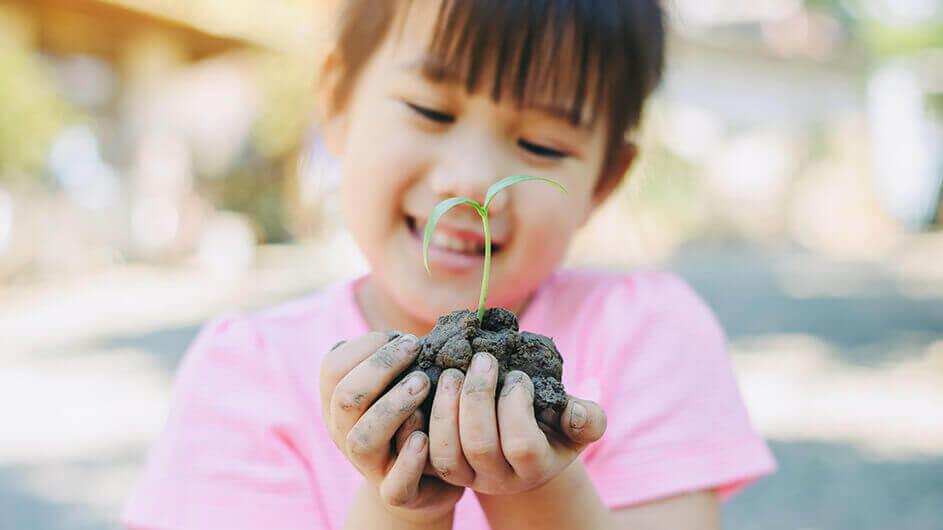 Ein Mädchen hält lächelnd Erde mit einem Pflanzenkeim in den Händen