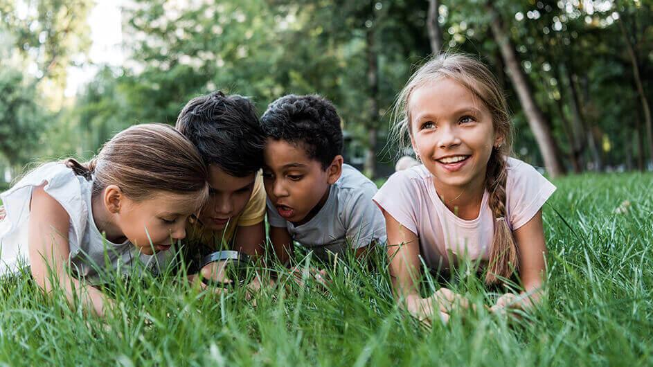Kinder liegen im Gras und beobachten staunend und lächelnd mit einer Lupe Insekten