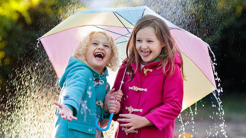 Zwei kleine, fröhlich lachende Kinder bei Regen unter einem Regenbogen-Regenschirm