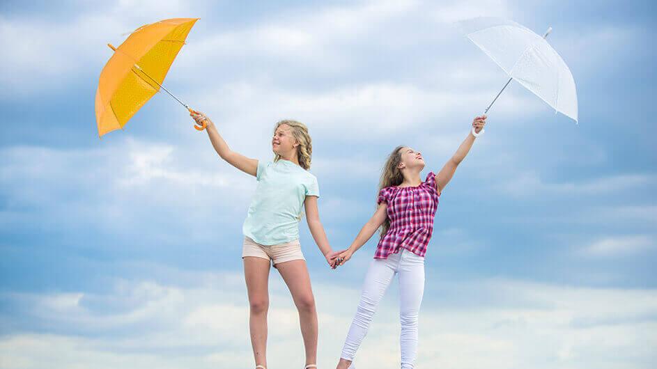 Zwei Mädchen stehen lächelnd mit Regenschirmen vorm wolkenverhangenen Himmel