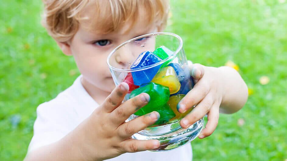 Ein kleiner Junge betrachtet bunte Eiswürfel in einem Glas