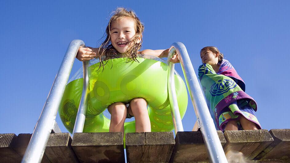 Zwei Kinder im Strandbad auf einem Steg: Ein Mädchen hat einen Schwimmreifen um, das andere ist gehüllt in ein Handtuch.