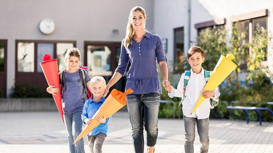 Eine Mutter geht mit ihren drei Kindern, die Schultüten halten, zur Einschulung. Alle vier lächeln fröhlich.