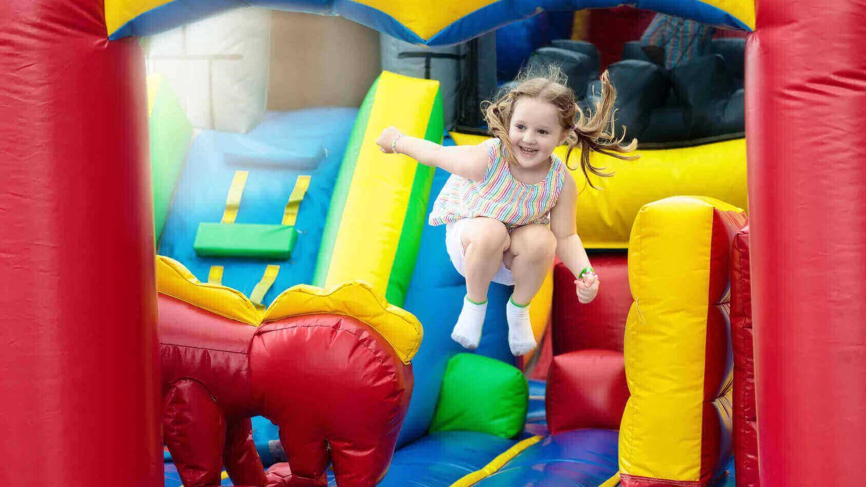 Mädchen springt auf einer Hüpfburg in einem Indoorspielplatz