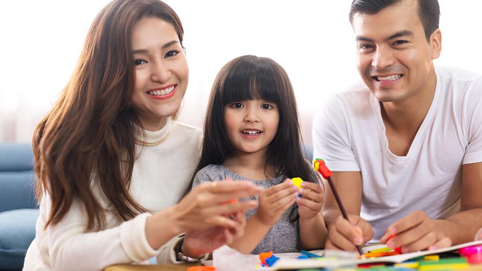 Eltern spielen mit ihrer Tochter mit bunter Knete. Alle drei lächeln.