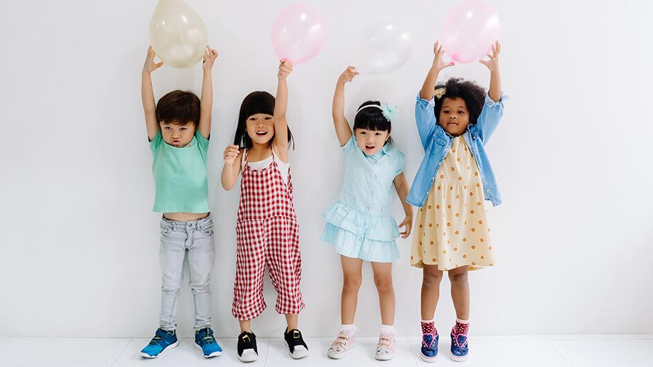Vier kleine Kinder spielen mit Luftballons