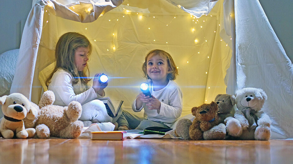 Zwei kleine Kinder in einer Höhle aus Decken mit Taschenlampen und Kuscheltieren