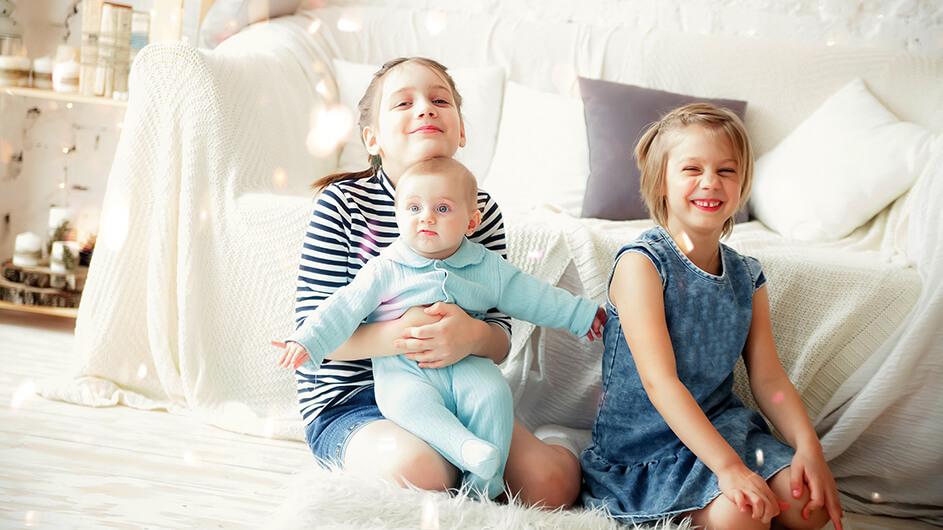 Drei Geschwister sitzen fröhliche zu Hause auf dem Boden