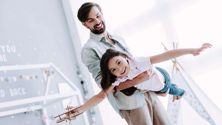 Ein Vater spielt mit seiner Tochter Flugzeu