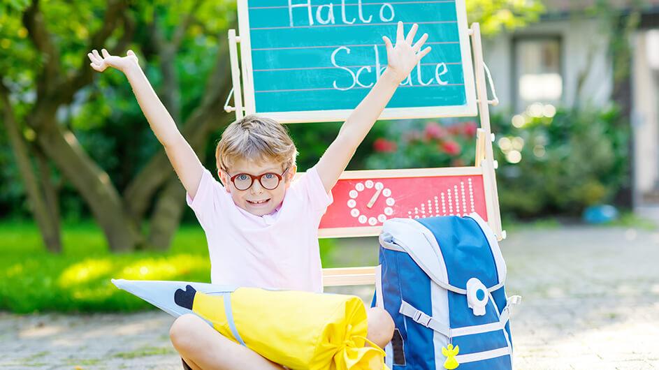 Fröhlicher Schuljunge bei seiner Berliner Einschulung mit Schultüte und Schulrucksack vor Schultüte